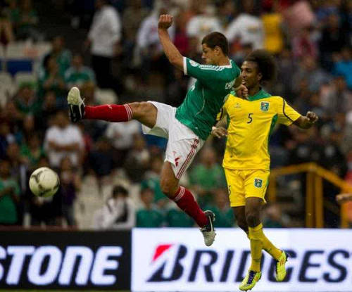 "Photo: Mexico and Real Madrid star Javier ""Chicharito"" Hernandez (left) contests the ball with Guyana's Walter Moore during the 2014 World Cup qualifying campaign."