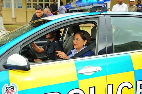 Photo: Prime Minister Kamla Persad-Bissessar takes a lift in a police car. (Courtesy UNCTT.org)