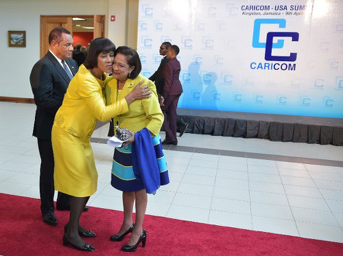 Photo: Former Trinidad and Tobago Prime Minister Kamla Persad-Bissessar (right) and former Jamaica Prime Minister Portia Simpson-Miller greet each other at a Caribbean Community (CARICOM) leaders meeting at the University of the West Indies on 9 April 2015 in Kingston. (Copyright AFP 2016/Mandel Ngan)