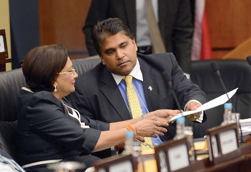 Photo: Prime Minister Kamla Persad-Bissessar (left) and Leader of Government Business Roodal Moonilal presumably discuss Parliamentary morality. (Courtesy Baltimore Post)