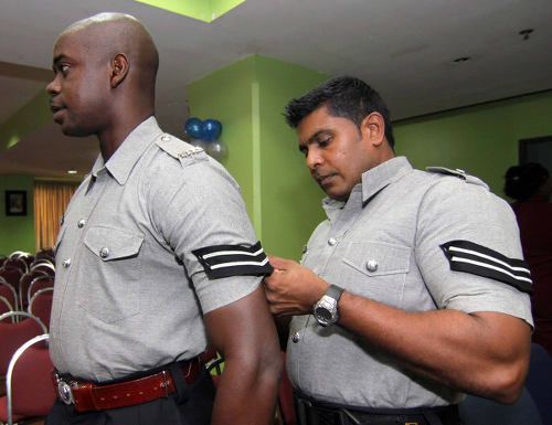 Photo: A police officer helps his colleague with his stripes.