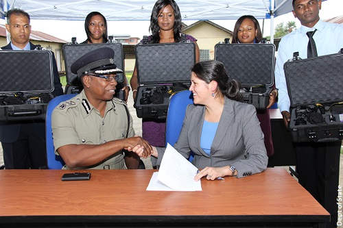 Photo: Acting Police Commissioner Stephen Williams (left) shakes hands with US Embassy Security Policy and Assistance Coordinator, Juanita Aguirre, at the handing over ceremony of 18 forensic photography kits to the Trinidad and Tobago Police Service by the US in 2015. (Courtesy US Embassy)