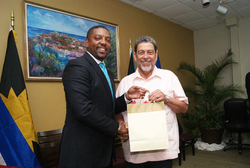 Photo: West Indies Cricket Board (WICB) president Dave Cameron (left) presents a token to St Vincent and the Grenadines Prime Minister Dr Ralph Gonsalves during a WICB-CARICOM meeting. (Courtesy Windies Cricket)
