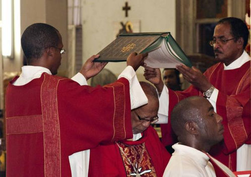 Photo: Archbishop Joe Harris (centre) is ordained. That is not the church's accounting ledger. (Courtesy News.gov.tt)