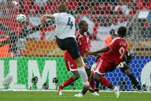 Photo: Former England star Steven Gerrard (left) drives home his country's second and final goal in their 2006 World Cup win over Trinidad and Tobago. Looking on are Aurtis Whitley (right) and Dennis Lawrence. (Copyright Robert Schmidt/AFP 2015)
