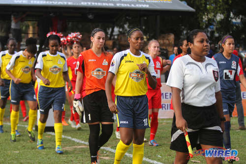 Photo: Fuego captain Tasha St Louis (centre) leads out her team for the Women's Premier League opener. At her right is Fuego goalkeeper Leticia Bussato. (Courtesy Sinead Peters/Wired868)