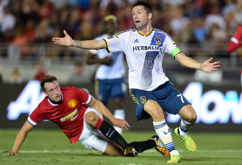 Photo: LA Galaxy star Robbie Keane (right) and Manchester United's Phil Jones clash in a friendly fixture. (Copyright AFP 2015)