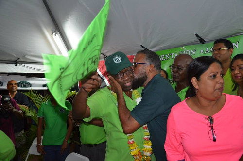 Photo: ILP political leader Jack Warner (centre) gets a kiss from an enthusiastic supporter during a cottage meeting in 2015.