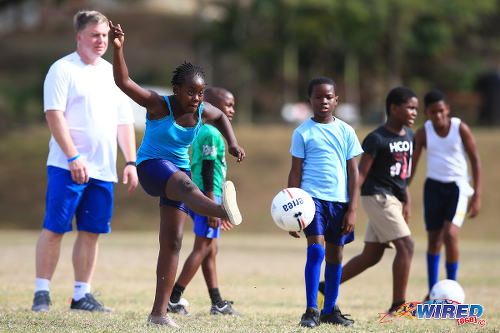 Photo: Former Chelsea midfielder Gareth Hall (background) offers shooting tips for children during a Tobago Legends training camp in Speyside, Tobago. (Courtesy Allan V Crane/Wired868)