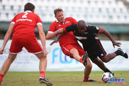 Photo: Henchoz the hatchet man? Liverpool defender Stephane Henchoz (centre) dishes it out to Caribbean All Stars player Paul Hall during the British Airways Tobago Legends Football Challenge final. (Courtesy Allan V Crane/Wired868)
