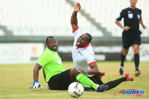 Photo: Caribbean All Stars striker Stern John (right) appeals successfully for a penalty after a collision with Chelsea guest player and goalkeeper Richard Goddard in the 2015 Tobago Masters competition. (Courtesy Allan V Crane/Wired868)