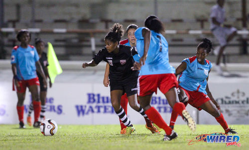 Photo: Petrotrin Oilers striker Kayla Taylor (centre) takes on the Wave defence during 2015 WPL action at Palo Seco. (Courtesy Allan V Crane/Wired868)