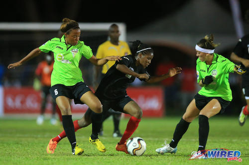 Photo: Oilers midfielder Shenelle Henry (centre) runs at Rush midfielder Pri (right) and Tamika Isaac in WPL action.. (Courtesy Allan V Crane/Wired868)