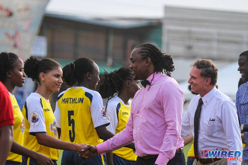 Photo: Sport Minister Brent Sancho (centre) shakes hands with Fuego defender Ermelinda Izquierda before the WPL opening game. (Courtesy Sinead Peters/Wired868)