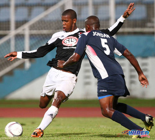 Photo: Former Central FC striker Dwight Quintero (left) tries to fire a shot past Defence Force player Devin Jordan during the 2013/14 Pro League season. (Courtesy Allan V Crane/Wired868)