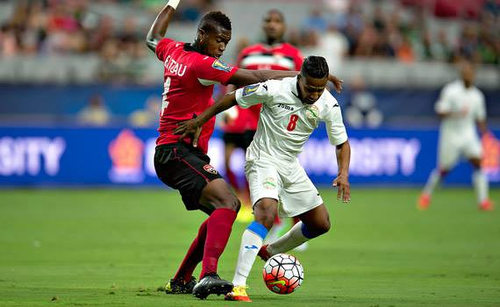 Photo: Trinidad and Tobago defender Sheldon Bateau (left) tackles Cuba midfielder Alberto Gomez in 2015 CONCACAF Gold Cup action. (Courtesy CONCACAF)