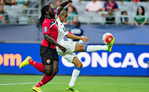Photo: Trinidad and Tobago captain Kenwyne Jones (left) harasses Cuba captain Yenier Marquez during their 2015 CONCACAF Gold Cup clash. (Courtesy CONCACAF)