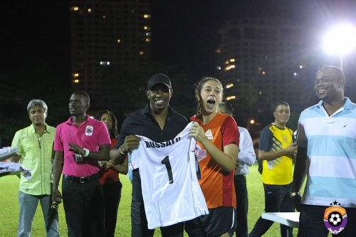 "Photo: Fuego goalkeeper Lele (centre) receives her WPL All-Star shirt from Trinidad and Tobago cricket star Dwayne Bravo while former ""Soca Warriors"" star Stern John (right) looks on. (Courtesy Sinead Peters/Wired868)"