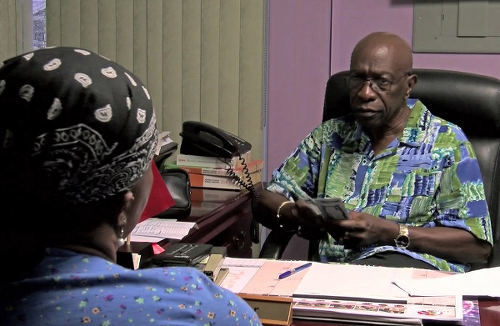 Photo: ILP political leader and ex-FIFA vice president Jack Warner offers money to a constituent. (Copyright Diego Urdanete/AFP 2015)