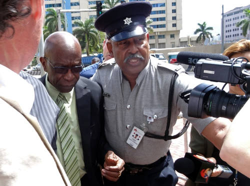 Photo: Chaguanas West MP and ex-FIFA vice president Jack Warner (left) gets a police escort as he arrives in Parliament on 5 June 2015. (Copyright Diego Urdaneta/AFP 2015)