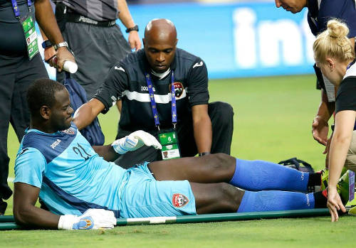 Photo: Trinidad and Tobago goalkeeper Jan-Michael Williams is helped on to the stretcher by physio Saron Joseph during their 2015 Gold Cup fixture against Cuba. (Courtesy CONCACAF)