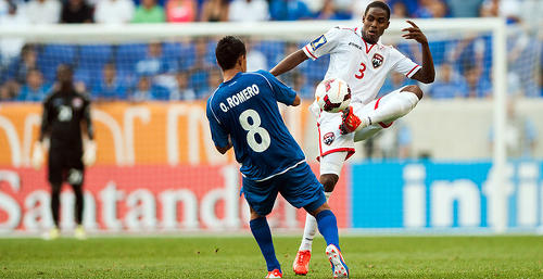 Photo: Trinidad and Tobago utility player Joevin Jones (left) in action against El Salvador's Osael Romero during the 2013 Gold Cup. (Courtesy CONCACAF)