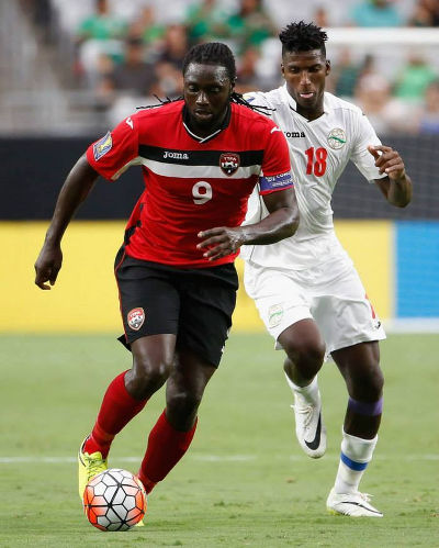 Photo: Trinidad and Tobago captain and forward Kenwyne Jones (left) accelerates past Cuba midfielder Daniel Luis during 2015 CONCACAF Gold Cup action. (Courtesy CONCACAF)