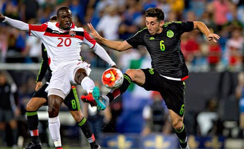 Photo: Trinidad and Tobago midfielder Keron Cummings (left) challenges Mexico midfielder Hector Herrera during CONCACAF Gold Cup action. (Courtesy CONCACAF)