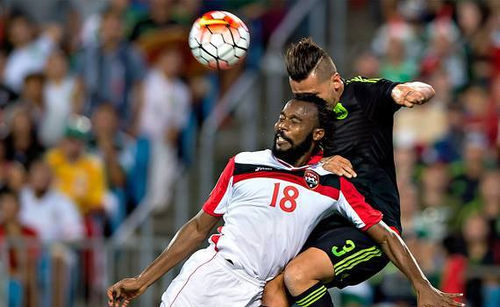 Photo Trinidad and Tobago defender Yohance Marshall (left) wins a header from Mexico defender Yasser Corona in CONCACAF 2015 Gold Cup action. (Courtesy CONCACAF)