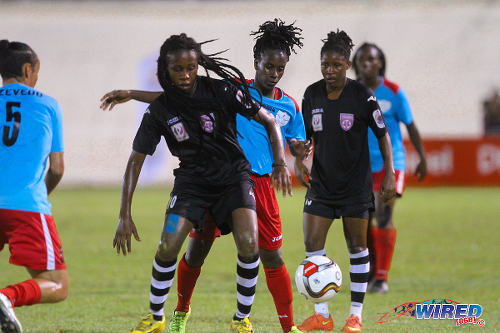 Photo: Petrotrin Oilers midfielder Naomie Guerra (centre) blocks the path of Wave FC captain Kennya Cordner during WPL action. Guerra is a member of the Trinidad and Tobago National Under-20 Team. (Courtesy Sinead Peters/Wired868)