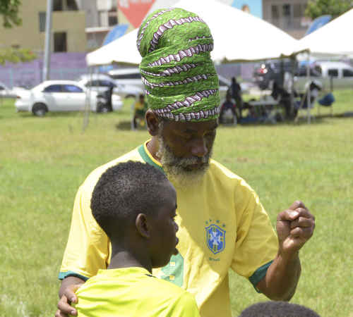 "Photo: Trendsetter Hawks coach Anthony ""Dada"" Wickham has a word with one of his players during 2015 Republic Bank National Youth Cup action at the Queen's Park Savannah. (Courtesy Allan Powder/Wired868)"