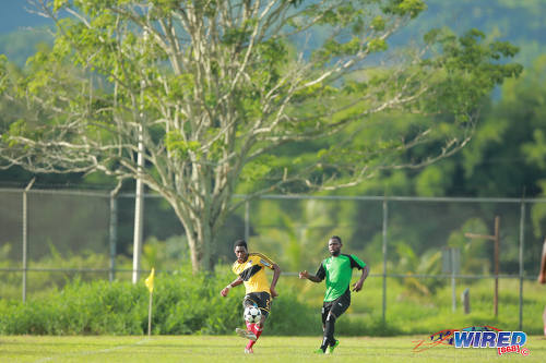 Photo: Cunupia FC defender Raymond Alleyne (left) passes the ball under pressure from Prisons FC attacker John Stewart in CNG Super League Championship Division action at the Youth Training Facility, Arouca. (Courtesy Allan V Crane/Wired868)