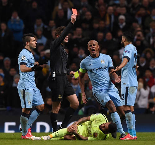 Photo: German referee Felix Brych (second from left) shows a red card to Manchester City defender Gael Clichy (right) while his teammates Vincent Company (second from right) and Sergio Aguero protest. On the floor is Barcelona defender Dani Alves. (Copyright AFP 2015)