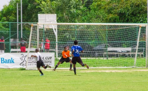 Photo: A Crown Trace FC attacker (left) squeezes his shot past the Todd's Road goalkeeper during Republic Bank National Youth Cup action. (Courtesy Republic Bank)