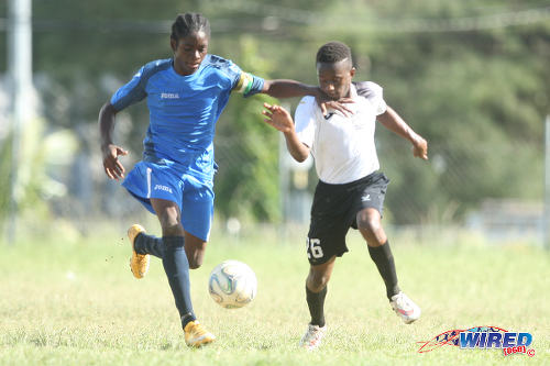 Photo: The Uprising Youths captain (left) tries to hold off a Crown Trace FC attacker during the Republic Bank National Youth Cup quarterfinals. (Courtesy Allan V Crane/Wired868)