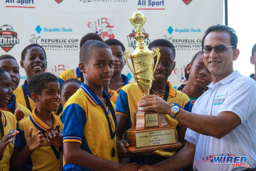 Photo: Republic Bank Risk Department manager Vijay Ragoonanan (right) hands the National Youth Cup Under-13 trophy to SKHY FC. (Courtesy Sinead Peters/Wired868)