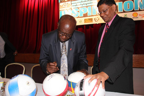 Photo: Former Chaguanas West MP and FIFA vice president Jack Warner (left) signs footballs for Trinidad Guardian sport editor Valentino Singh. (Copyright Guardian.co.tt)