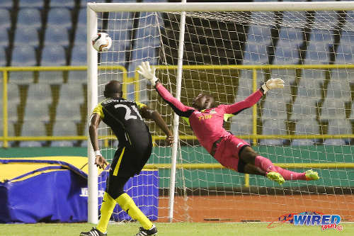 Photo: Defence Force FC goalkeeper Sheldon Clarke (right) dives in vain at an effort from St Ann's Rangers midfielder Miguel Romeo during Pro League action. Looking on is Defence Force left back Aklie Edwards. (Courtesy Chevaughn Christopher/Wired868)