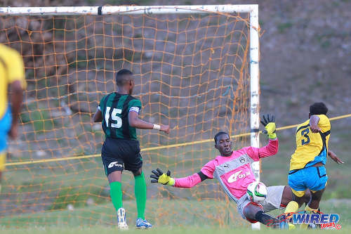 Photo: Carapichaima East Secondary goalkeeper Jeremiah Phillips (centre) denies Speyside High School's Jakeb Douglas in 2015 SSFL action in Speyside, Tobago. (Courtesy Allan V Crane/Wired868)