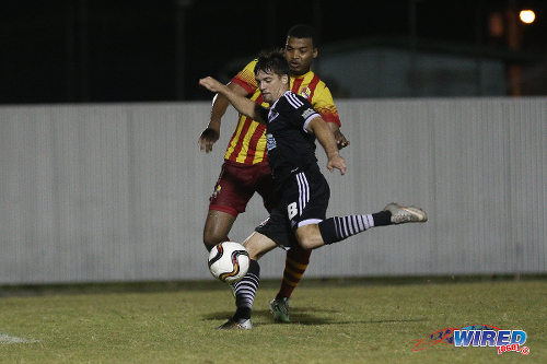 Photo: Central FC midfielder Sean De Silva (foreground) volleys home his double while Point Fortin Civic left back Andrei Pacheco looks on at the Mahaica Oval on 26 September 2015. (Courtesy Chevaughn Christopher/Wired868)