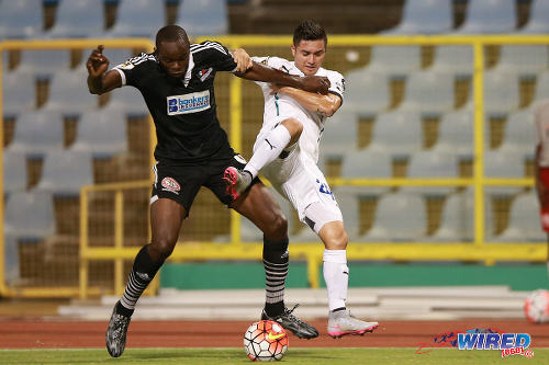 Photo: Central FC defender Andre Ettienne (left) brushes aside Comunicaciones attacker Carlos Figueroa during CONCACAF Champions League action at the Hasely Crawford Stadium, Port of Spain on 17 September 2015. (Courtesy Allan V Crane/Wired868)