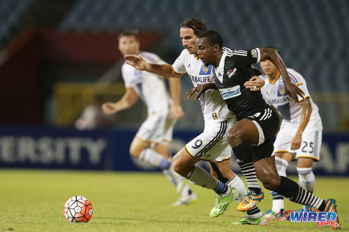 Photo: Central FC attacker Marcus Joseph (right) and LA Galaxy striker Allan Gordon chase the ball during CONCACAF Champions League action last night. (Courtesy Allan V Crane/Wired868)