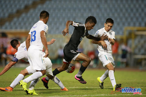 Photo: Central FC striker Willis Plaza (centre) charges through the centre of the Comunicaciones defence during 2015 CONCACAF Champions League action. (Courtesy Allan V Crane/Wired868)