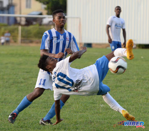 Photo: Naparima College attacker Jeremiah Kesar (foreground) flicks the ball while St Mary's College midfielder Bryant Van Low looks ok. (Courtesy DPI Photography/Wired868)