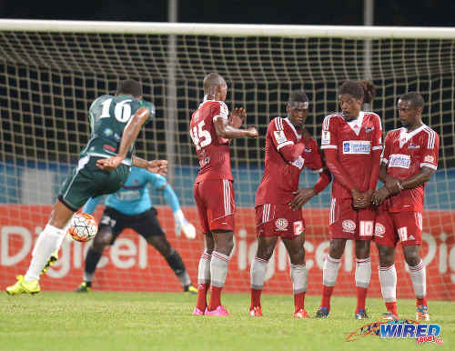 Photo: W Connection captain Alvin Jones (far left) blasts a free kick towards goal during the 2015 Digicel Charity Shield. Looking on (from right) are Central FC players Marcus Joseph, Marvin Oliver, Elton John, Ataulla Guerra and Jan-Michael Williams. (Courtesy DPI Photography/Wired868)