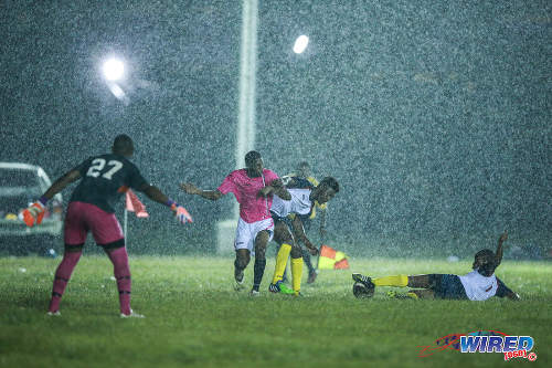 Photo: Malabar FC attacker Che Edwards (second from left) struggles with Edinburgh defender Aswad Alves (centre) while Shaheed John (right) slides in to win the ball during CNG National Super League  Championship Division action at the D'abadie Recreation Grounds.  Looking on is Edinburgh goalkeeper Joel Sansavior. (Courtesy Allan V Crane/Wired868)