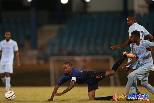 Photo: Petit Valley captain Karamo Samuel (centre) tumbles to the ground during CNG National Super League action yesterday at the Queen's Park Oval. (Courtesy Allan V Crane/Wired68)