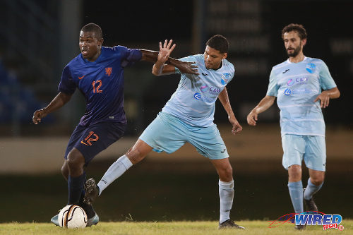 Photo: Petit Valley midfielder David Charles (left) holds off a QPC player (centre) while Benedict Barrett looks on in CNG NSL action at the Queen's Park Oval. (Courtesy Allan V Crane/Wired868)