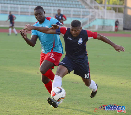 Photo: Police FC's Jason Boodram (right) holds off Marabella Family Crisis Centre's Ghmyo Harper during a 2015/16 CNG NSL Premiership Division contest. (Courtesy DPI Photography/Wired868)