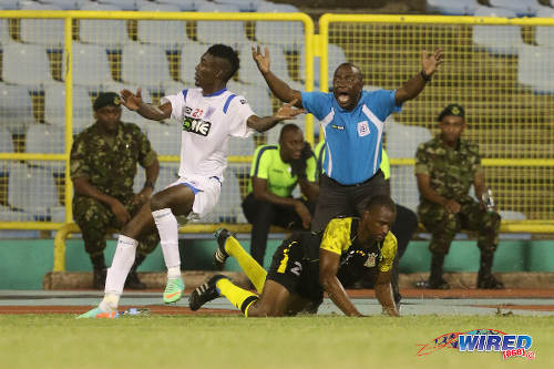 Photo: St Ann's Rangers coach Angus Eve rages at the referee after his player Sayid Freitas (left) is whistled for a foul on Defence Force stopper Glynn Franklin in yesterday's Pro League affair. (Courtesy Chevaughn Christopher/Wired868)